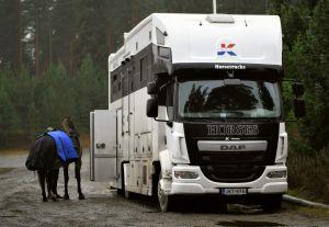 Ryttaren John Antell med häst bredvid hästtransportbilen.