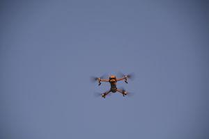 Närbild på en flygande drönare tagen nerifrån mot en blå himmel.