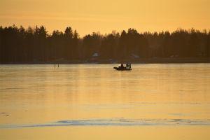 En hydrokopter kör över isen. Solen håller på att gå ner och färgar allt gult. I bakgrunden syns skogbeklädd strand.