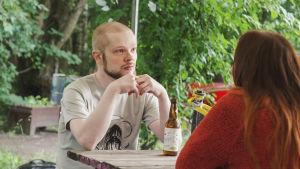 Skallig man i ljus t-skjorta sitter vid bord med ölflaska.