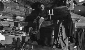 Kansatieteilijä Sakari Pälsi istuu laverilla metsätyömaan pirtissä Rovaniemellä vuonna 1923.