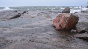 En strand med stora släta stenar. Stora vågor slår mot stenarna. Ovanpå klipphällen finns vatten som krusar sig i vinden.