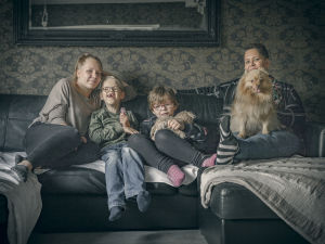 Familjen Jääskeläinen sitter i soffan.
