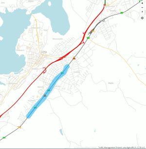 En karta med vit bakgrund och ljusgråa streck för vägar, ett tjockare rött streck för en huvudväg och sedan ett svart streck för järnväg. På järnvägslinjen har en strecka målats med ljusblå färg i ett fält längs med sträckan.