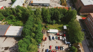 Luftbild över småindustriområde med grönområde kantat av parkeringsplats, gata och hus i rödtegel.