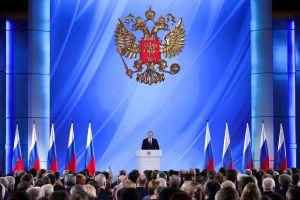 En stor blå bakgrund med en dubbelörn och en man i en talarstol omgiven av ryska flaggor. I förgrunden huvuden tillhörande publiken. President Vladimir Putin talar om läget i nationen.