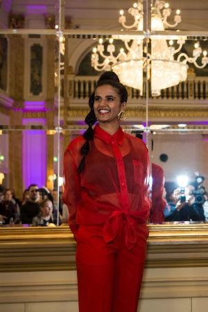 UMK-finalisti Tika poseeraa hymyillen punaisessa housupuvussa Kämpin Peilisalissa.