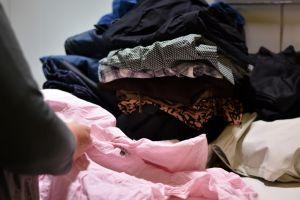 Hög av kläder och skymten av handen på en som sorterar kläderna.