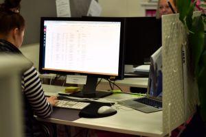 Kvinna som sitter vid en dator och arbetar.