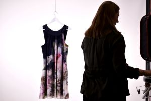 Siluett av kvinna som fotograferar en upphängd klänning.