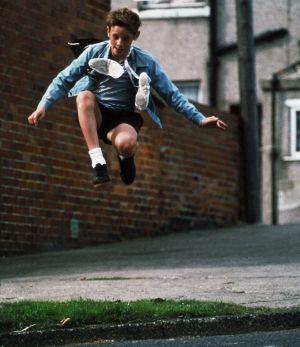 Billy Elliot (Jamie Bell) hyppäämässä ilmaan balettitossut kaulan ympäri kietaistuna.