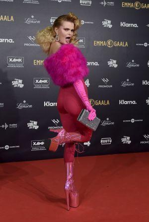 EN kvinna i rosa kläder och skyhöga klackskor.