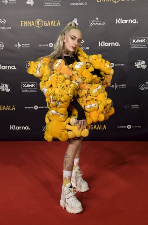 En blond kvinna i en klänning konstruerad av mjukisdjur.