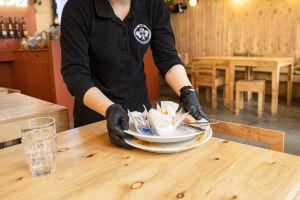 Thai Street Foodin työntekijä kerää lautasia pöydästä.