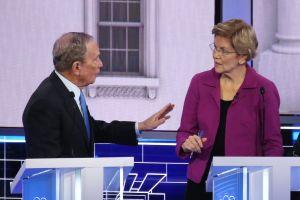 En gråhårig man i kostym håller upp handen mot en blond kvinna i glasögon. Båda står bakom podier.