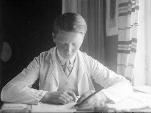 Teini-ikäinen Tauno Hannikainen on syventynyt kirjoitustehtävään pöydän ääressä. Kuva noin vuodelta 1910.