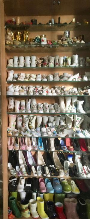 I ett sovrum inne i huset finns lite över 800 porslinsskor en av varje delvis insatta i skåp med glasdörrar.  Skorna är mest i porslin med även sten, trä, plast, läder, keramik, osv. Doris Hägg.