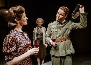 En ung man i tysk soldatuniform lyfter smidigt på hatten för en ung kvinna i klänning.