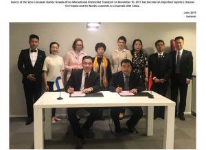 Två personer undertecknar ett avtal vid ett bord. Åtta personer står i bakgrunden.
