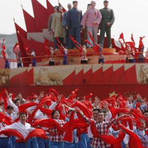 Personer i parad med röda flaggor.