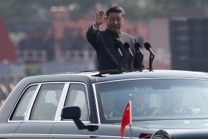 Kinas president Xi Jinping står upp i takluckan till sin limousin och gör en hälsningsrörelse.