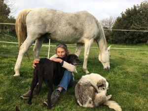 Kirsti Somersalo istuu hevosen ja koiriensa kanssa Rooman maaseudulla.