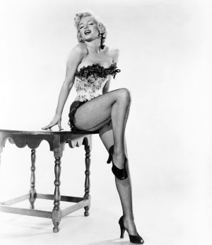 Marilyn Monroe eroottisessa asennossa pöydällä pienissä vaatteissa.