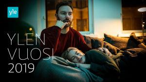 Nainen ja mies katselevat televisiota sohvalla. Kuvassa teksti Ylen vuosi 2019.