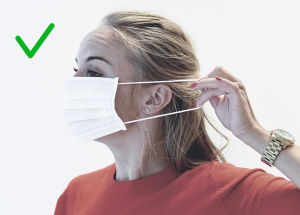Bild på rätt sätt att ta av sig ett munskydd. Man ska ta i banden, inte i själva skyddet.