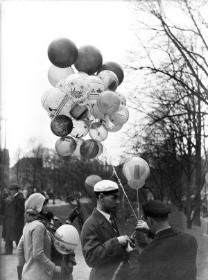 En svartvit gammal bild på en man i studentmössa med ett knippe ballonger i handen.