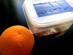 En förpackning med skolmat. Bredvid plastlådan sitter en apelsin.
