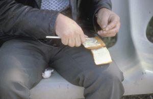 Köyhä mies istuu penkillä tekemässä voileipää (1985)