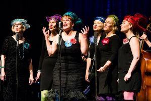 Tilannekuva: Merry ladies tyylikkäinä mustissa mekoissa ja iloisissa hatuissa laulamassa lavalla