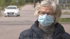 Äldre kvinna med munskydd.