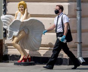 Manlig person med ansiksskydd går förbi Marilyn Monroe-staty.