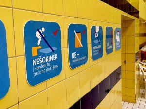 Varningsskyltar som bland annat förbjuder hopp i bassängen på väggen i en litauisk simhall.