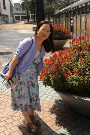 En kvinna står på en gata bredvid en blomrabatt.
