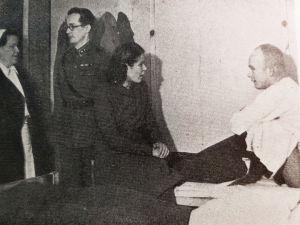 Anna Mutanen istuu potilaan sängyn laidalla sotasairaalassa.