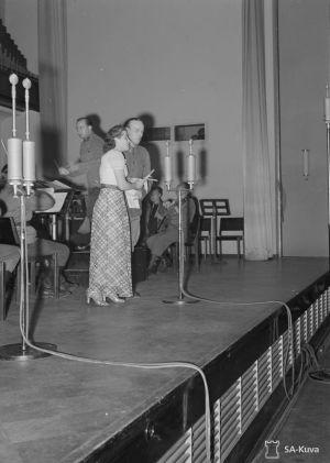 Oopperalaulaja Anna Mutanen ja näyttelijä Thure Bahne toivekonsertin solisteina Helsingin konservatorion salissa 30.7.1942. Korsuorkesteri säestää.