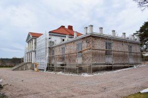 Den stora vita huvudbyggnaden på söderlångvik gård omgiven av byggställningen och med den vita rappningen nerknackad på flyglarna så att den gråröda tegelväggen är blottad.