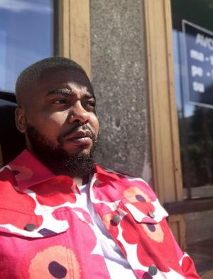 Seksikäs Suklaa eli Luyeye Konssi istuu seinän vierustalla punakukallinen Marimekon unikkokuosinen paita päällään