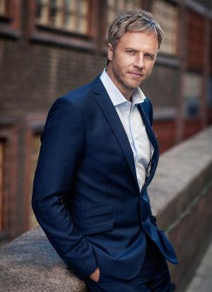 Författaren och den menatal tränaren Olof Röhlander poserar i blå kostym och vit skjorta.