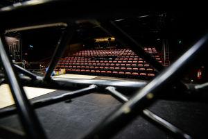 Rader av tomma stolar i en teatersal.