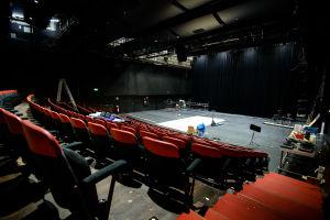 Teatersalen Klarascenen, med tomma bänkrader och renoveringsverktyg på scenen..