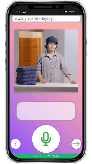 Kännykkä, jonka ruudulla on kuva Kielikylpy2.0 tilanteesta. Mies katsoo tiskin takaa käyttäjää ja alla on mikrofoni-kuvakkeella varustettu nappi.