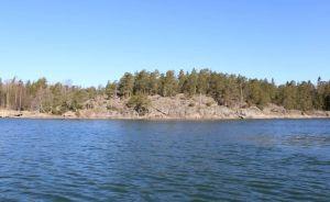 Ett berg vid havet. På berget växer många tallar. Vattnet är rätt stillsamt med bara små krusningar och en intensiv blå färg.