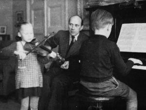 Taru Kumpunen 6 vuotta soittaa viulua isän ja veljen seurassa.