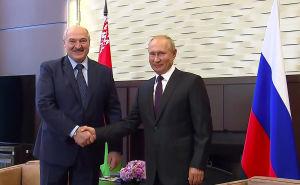Två män ler mot kameran medan de skakar hand. Männen är Rysslands president Vladimir Putin och Belarus president Aleksandr Lukasjenko.