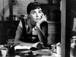 Mustavalkoinen kuva naisesta haaveilemassa kirjoituspöydän ääressä, ehkä päiväkirjaa kirjoittaen.