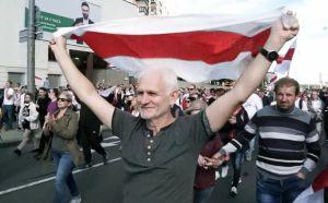 Ales Bialiatski går i tåg med människor omkring sig och håller upp den rödvita flaggan som används i demonstrationerna i Belarus.